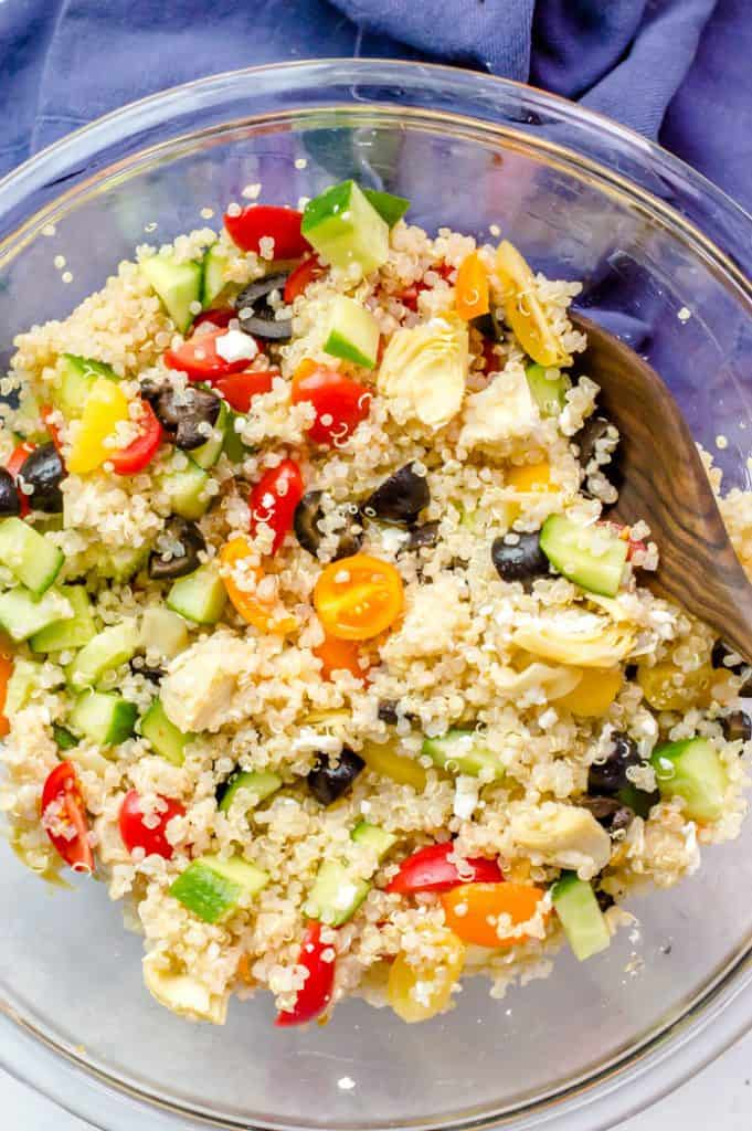 Greek Quinoa salad in a bowl right after being mixed. A wooden spoon is resting on the edge of the bowl.