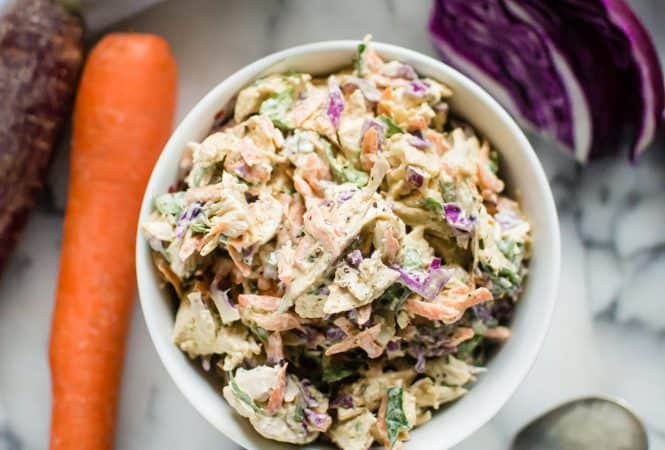 Overhead on the healthy Veggie-Loaded Spring Chicken Salad with carrot and cabbage on the sides