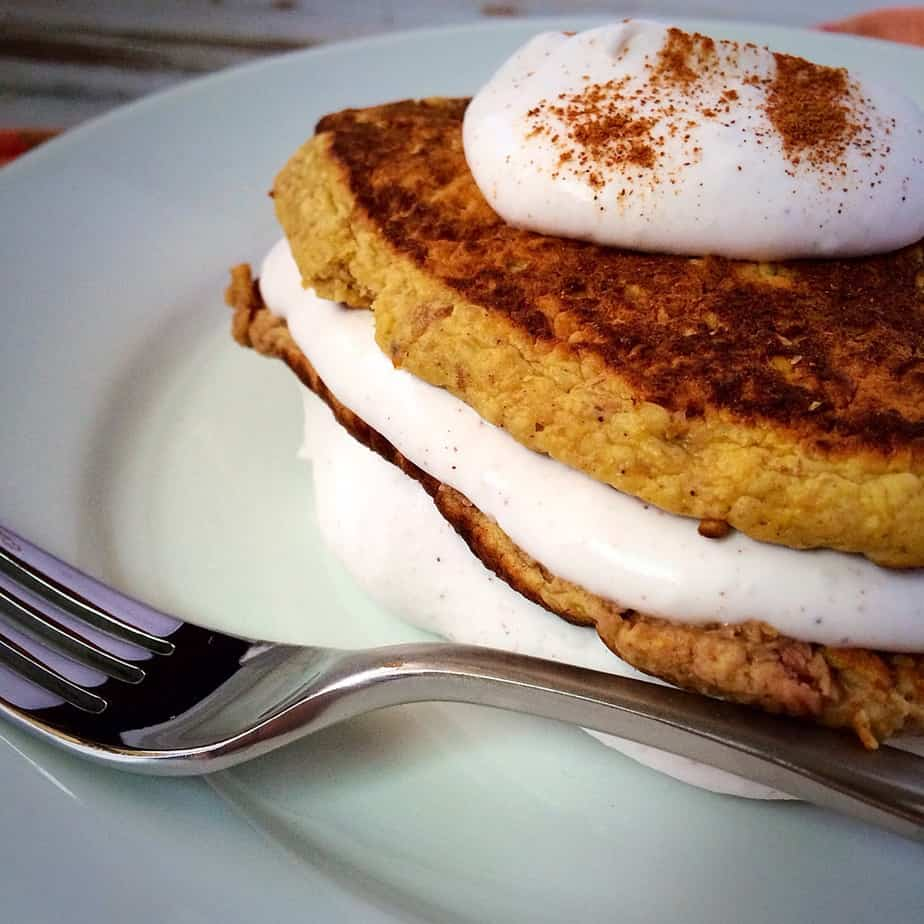 Pumpkin Pancakes with Cinnamon Whipped Coconut Cream served in a white plate with a metal fork on the side