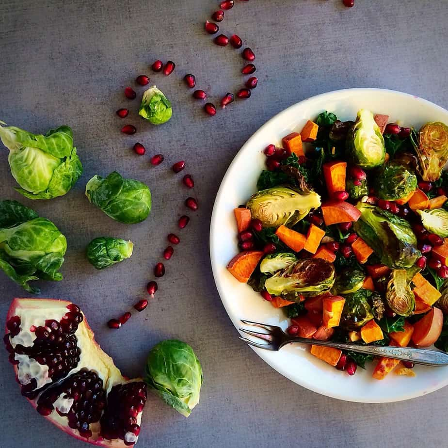 Warm Kale Salad with Pomegranate and Garlic Roasted Brussels Sprouts and Sweet Potatoes