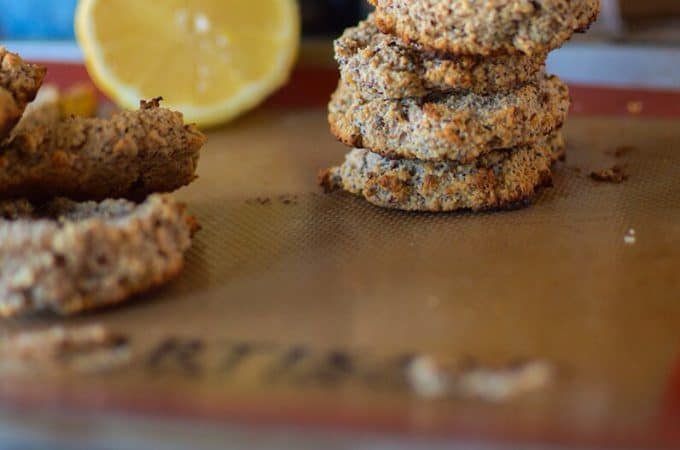 A stack of healthy and delicious Paleo Lemon Breakfast Cookies with a lemon wedge blurred in the background