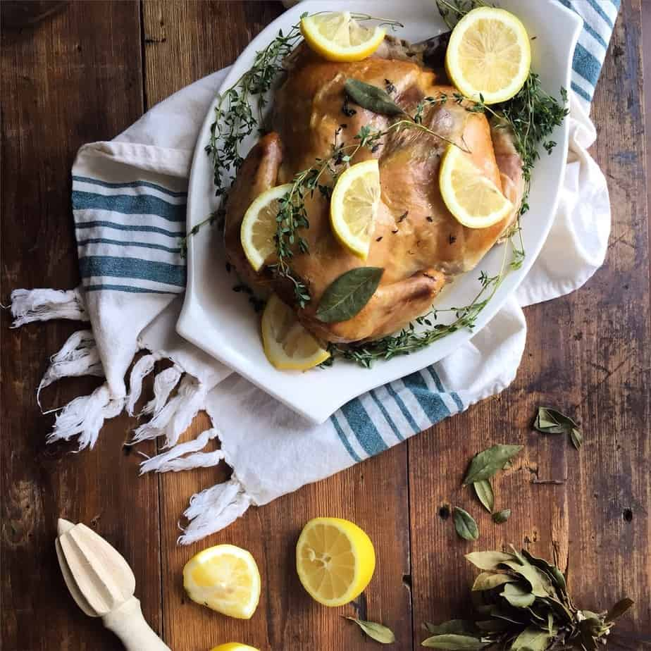 Ready Slow Cooker Lemon Thyme Whole Chicken on a wooden table, decorated with a white towel underneath the plate