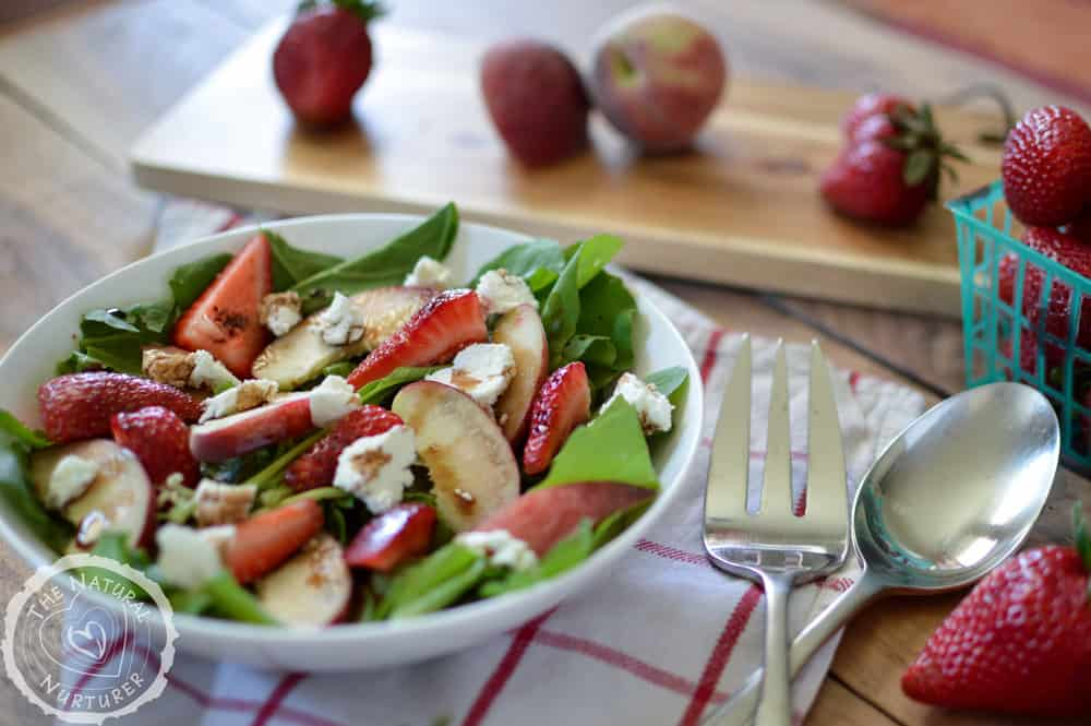 Side view of the delicious arugula salad with strawberry and peach served in a bowl with plenty of strawberries around