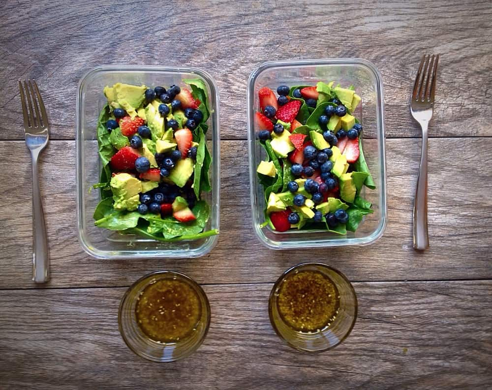 Berry avocado spinach salad in two glass storage containers with fork next to them. Poppyseed dressing is in small bowl next to the containers.