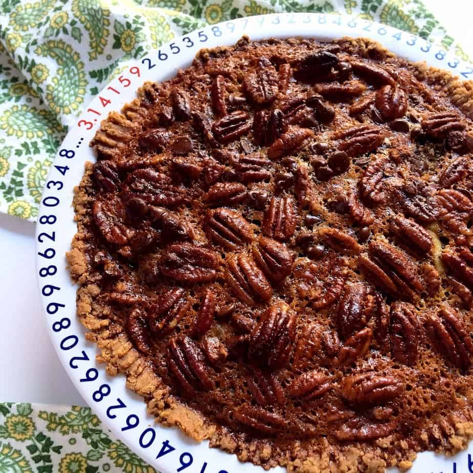Closeup of the chocolate maple pecan pie looking extra inviting and served on a big white plate.