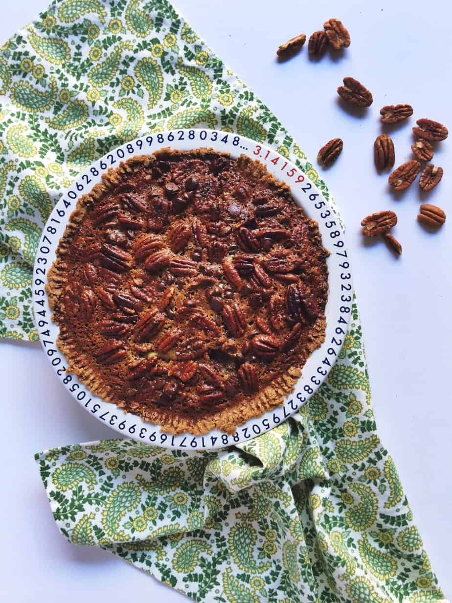 Overhead on the amazingly delicious chocolate maple pecan pie served with plenty of pecans around the dish.
