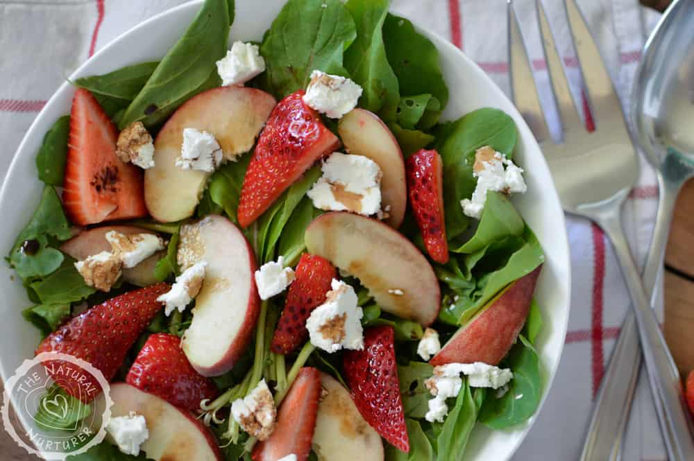 Closeup of the delicious peach and strawberry arugula salad with goat cheese and honey balsamic dressing