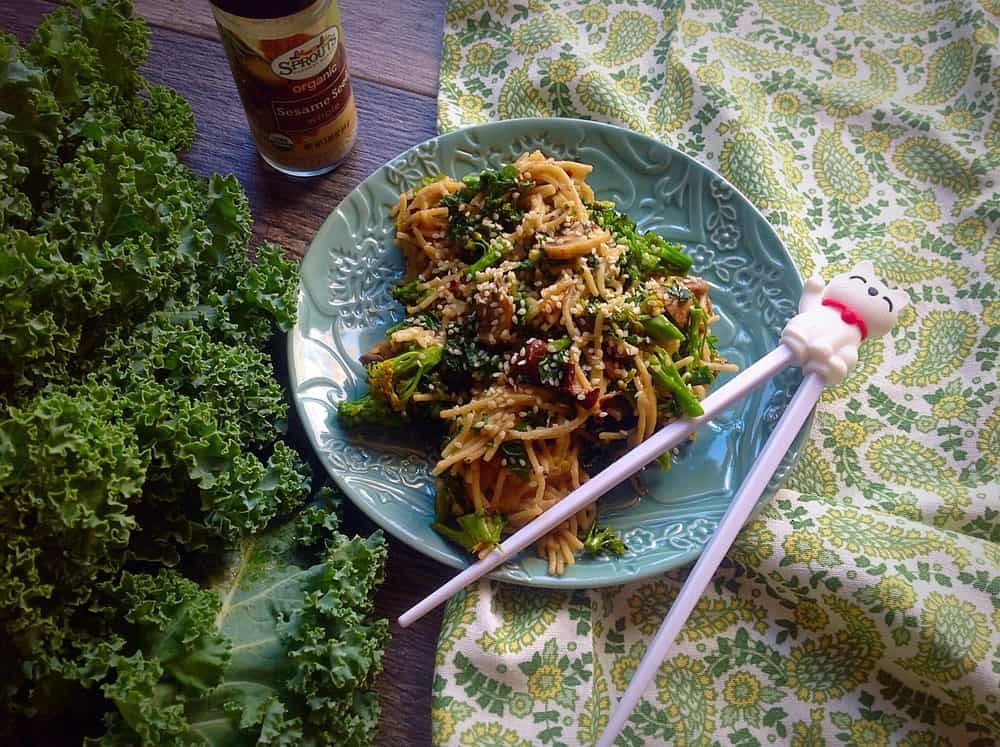 Spicy Pasta with Garlic, Broccoli, Kale & Mushrooms served on a big blue plate with chopsticks on top