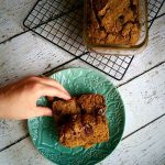 A left hand grabbing one of piece of the healthy Spelt Pumpkin Chocolate Chip Bread