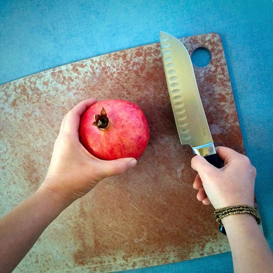 Cutting a pomegranate with a knife on a board
