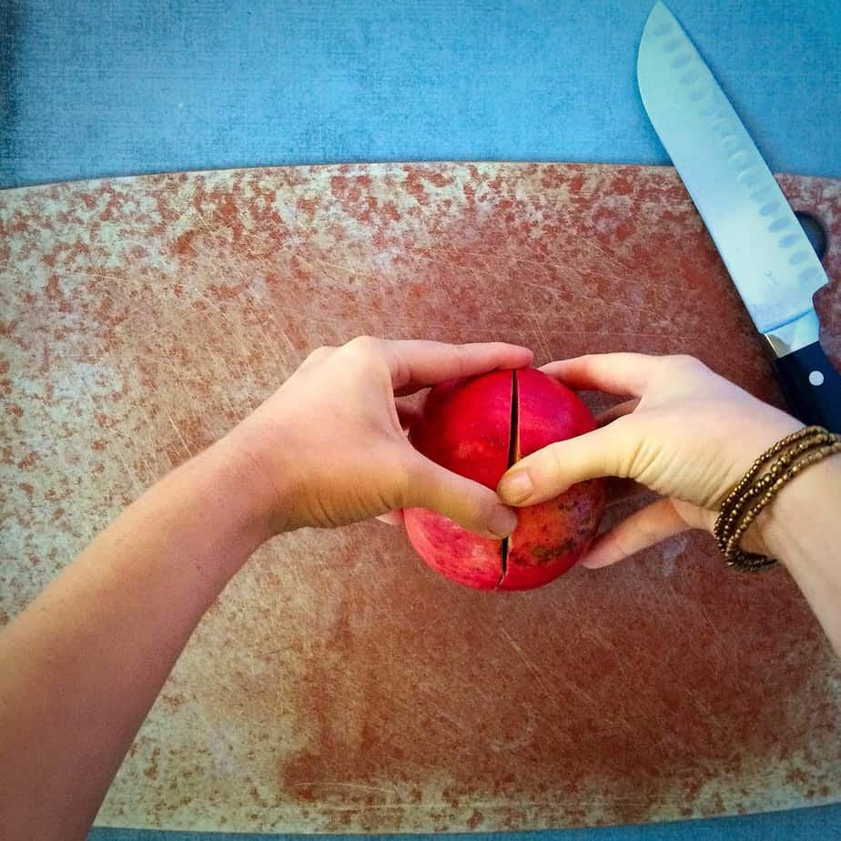 Using two hands to break the pomegranate in two halves
