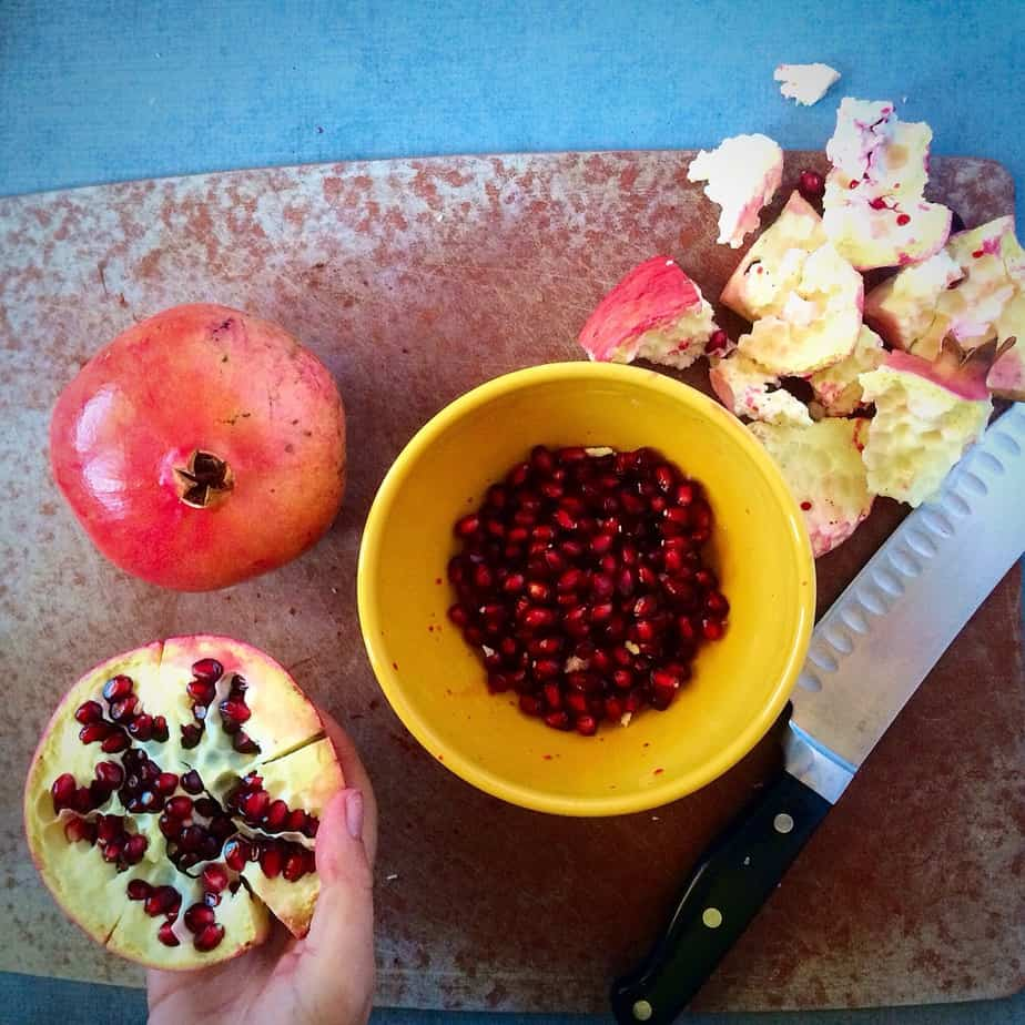 Showing How To Cut A Pomegranate using a knife and a cutting board.