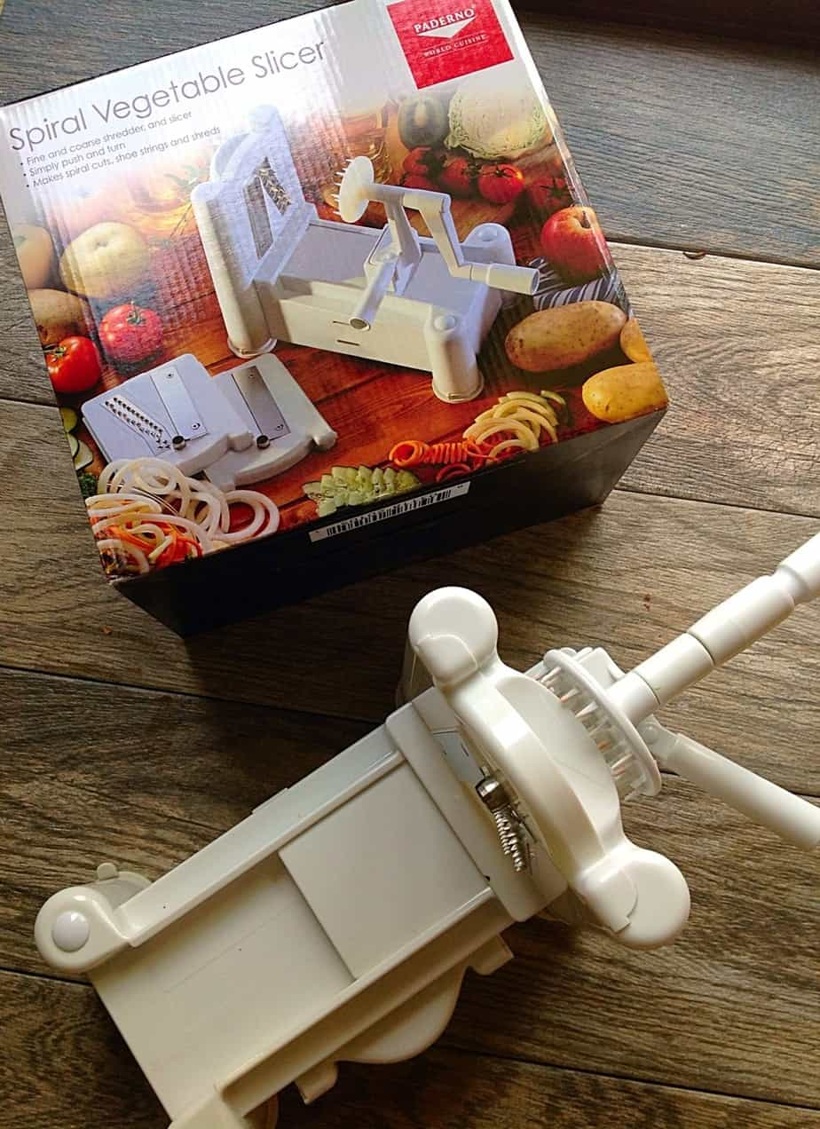 Spiral vegetable slicer with a box on top of a wooden table