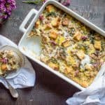 Sausage Leek & Mushroom Breakfast Casserole ready in a big tray and served in a small white plate with a fork on the top