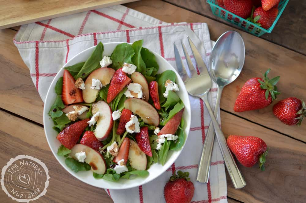 Peach and Strawberry Arugula Salad with Goat Cheese and Honey Balsamic Dressing served in a big white bowl with cutlery on the side