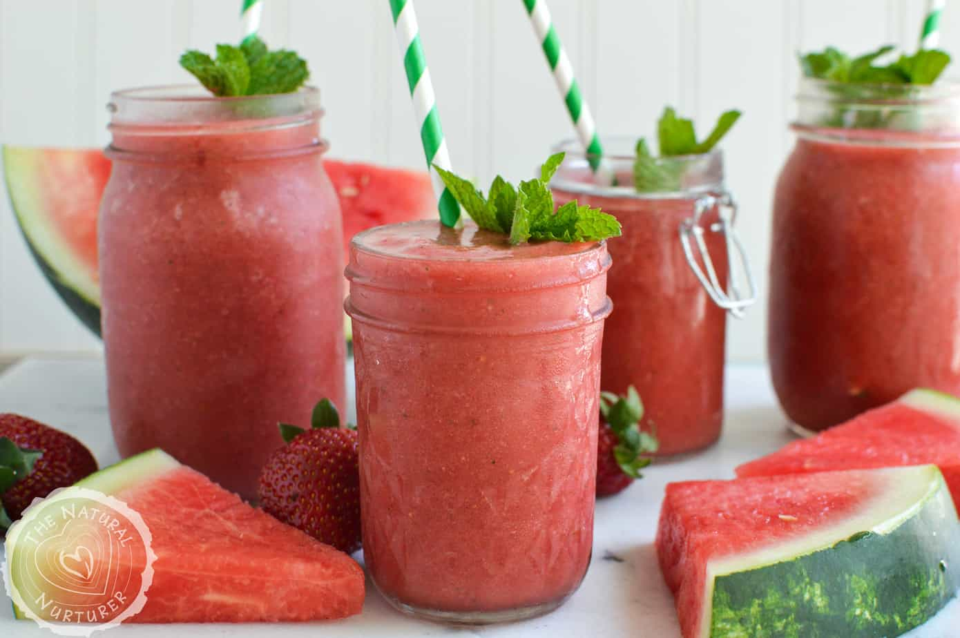 Closeup of the Watermelon Mint Slushies served in cute little jars with striped straws