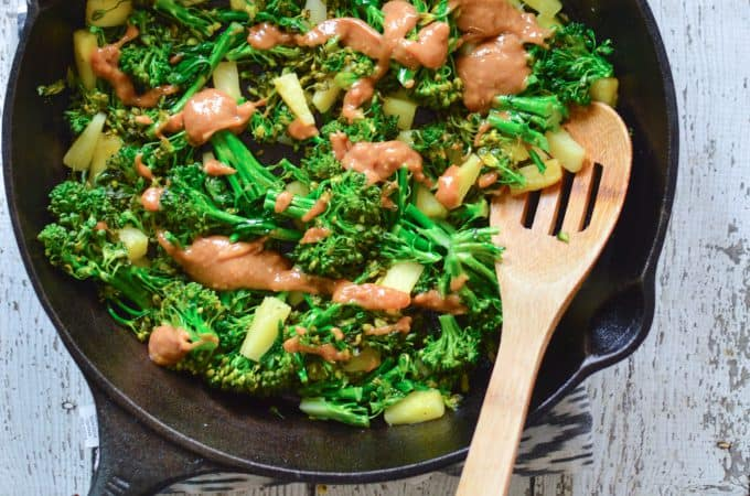 Pineapple Broccoli Stir Fry with Thai Peanut Sauce in a skillet served on a big white table