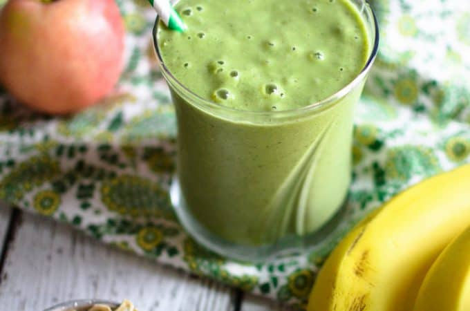 Power-Up Green Smoothie served in a cup with a straw inside and bananas and apple right next to it