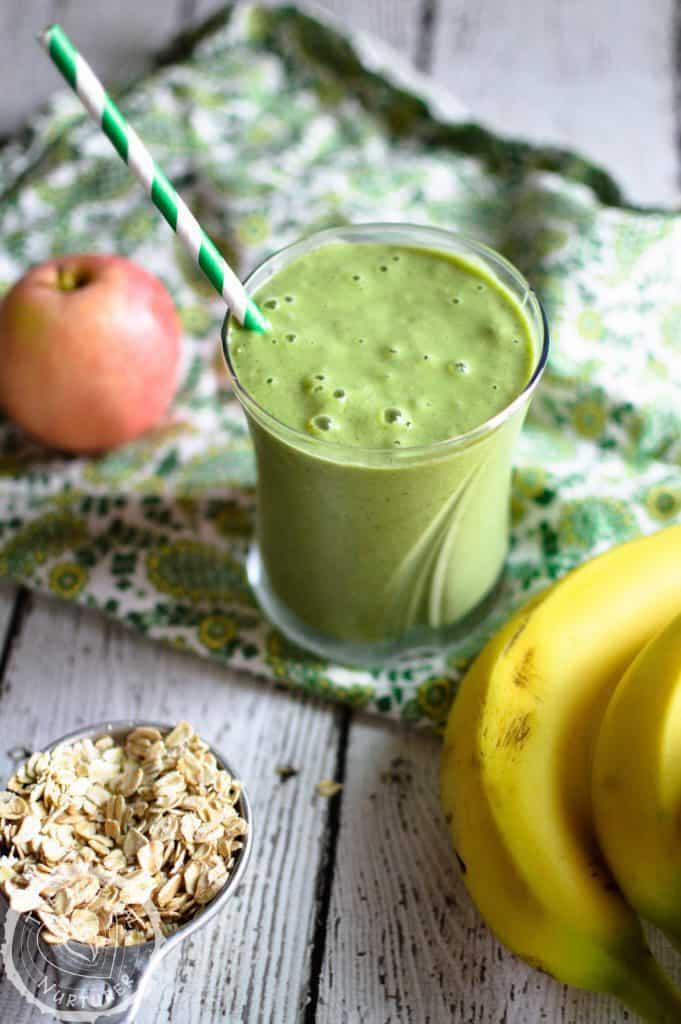 Power-Up Green Smoothie served in a glass with a straw inside and bananas and apple right next to it on a piece of nice cloth.