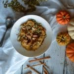 Overhead of the amazingly delicious, Fantasticly Fall Pumpkin Oats presented with raw pumpkins and cinnamon sticks around the bowl