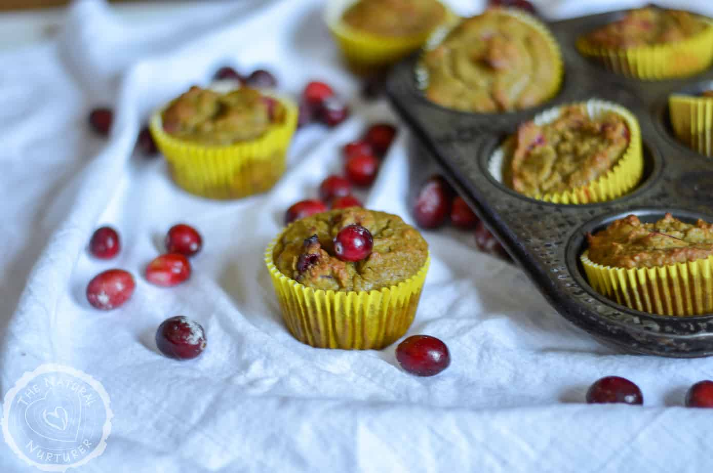 One of the Orange Cranberry Muffins in front of a stack of more muffins in the background.