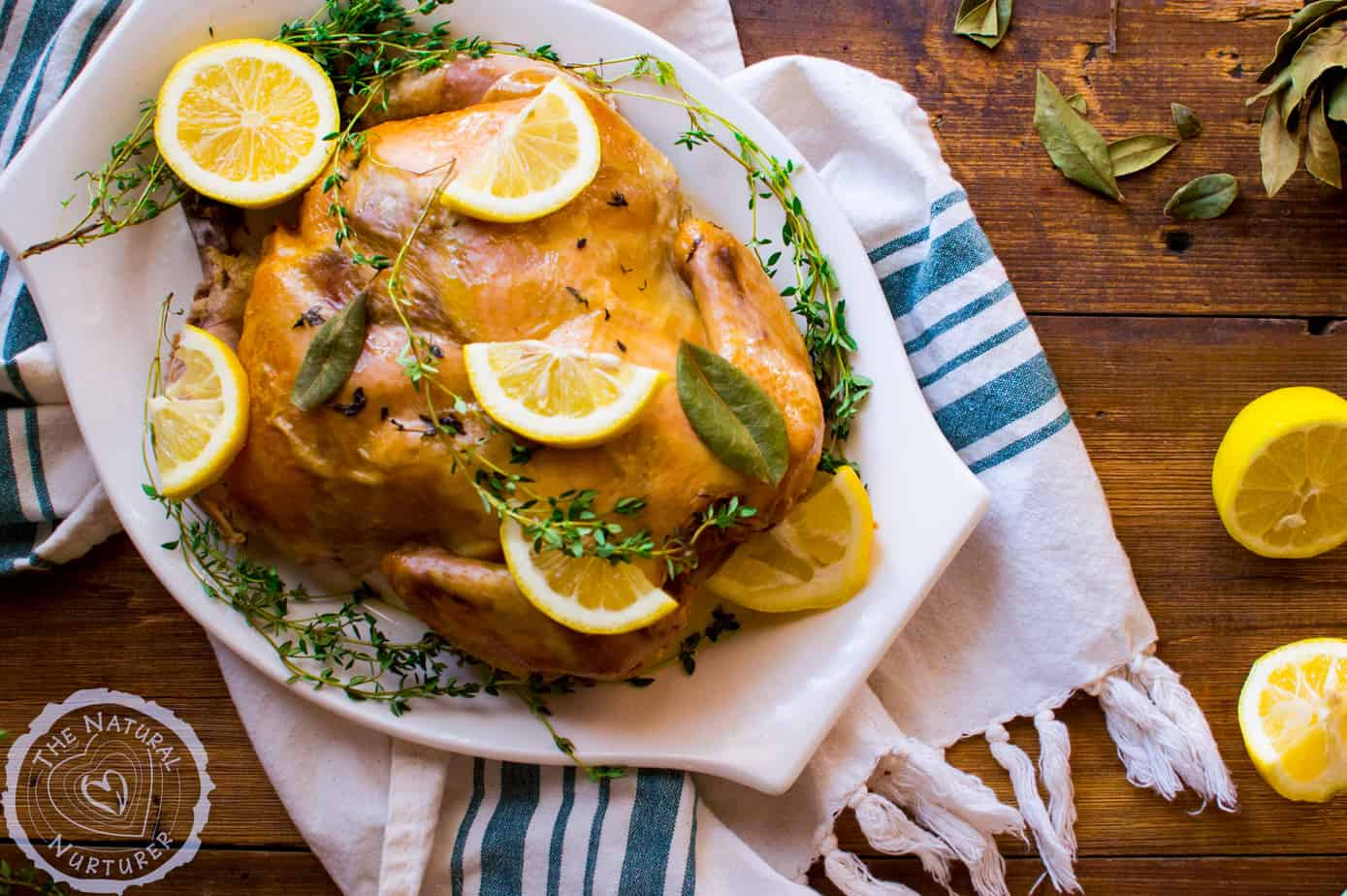 Closeup of the delicious slow cooker lemon thyme whole chicken decorated with lemons on a big white tray
