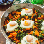 One-Skillet Sweet Potato & Kale Fries with Eggs served in a big pan with forks and strawberries in the background
