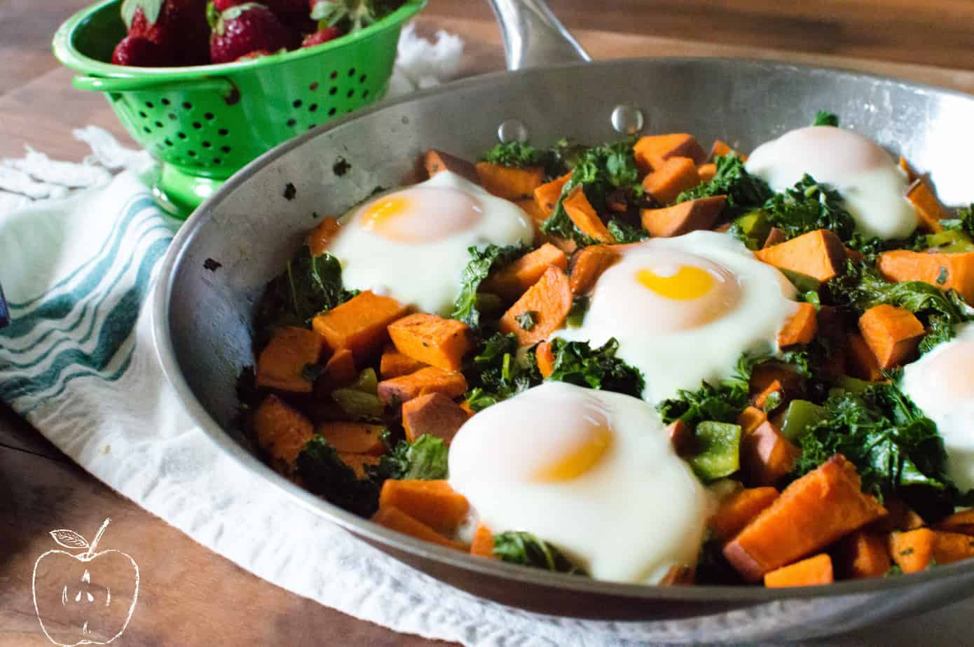 Side view of the healthy One-Skillet Sweet Potato & Kale Fries with Eggs served hot and fresh with strawberries in the background