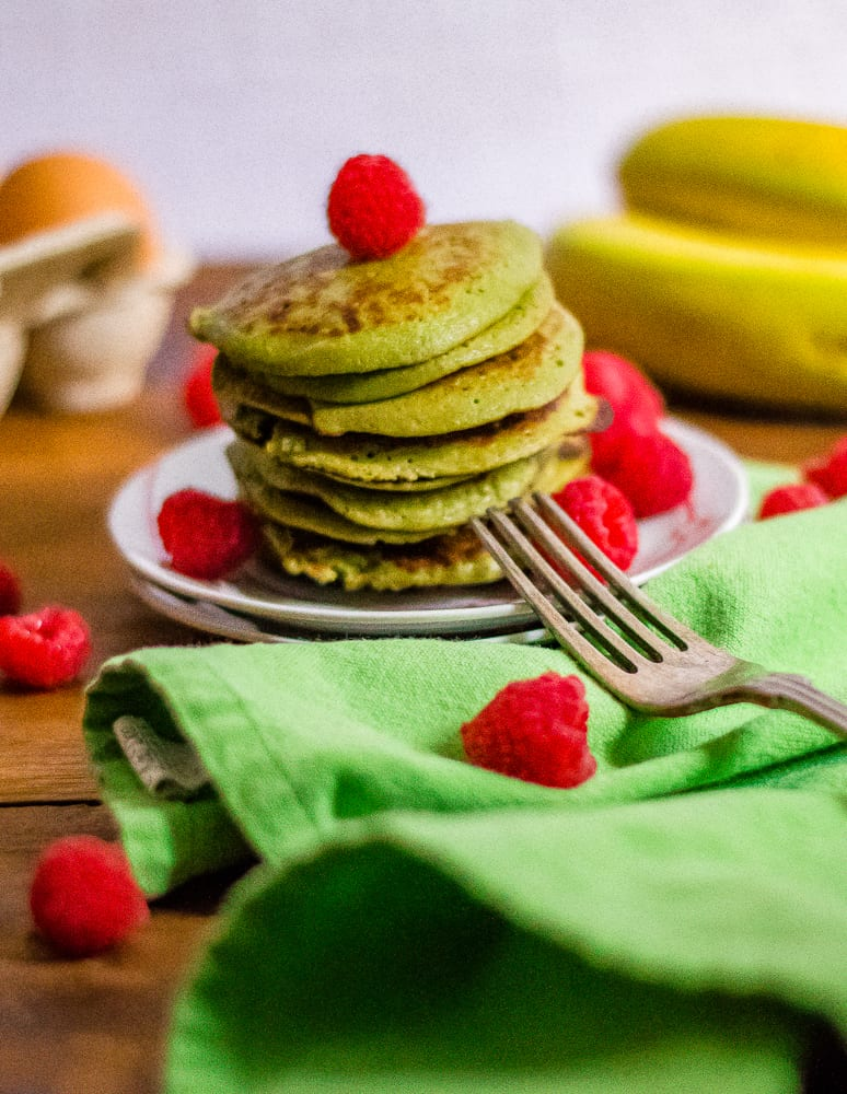 A big stack of Flourless Green Blender Pancakes topped with raspberries and served with a fork