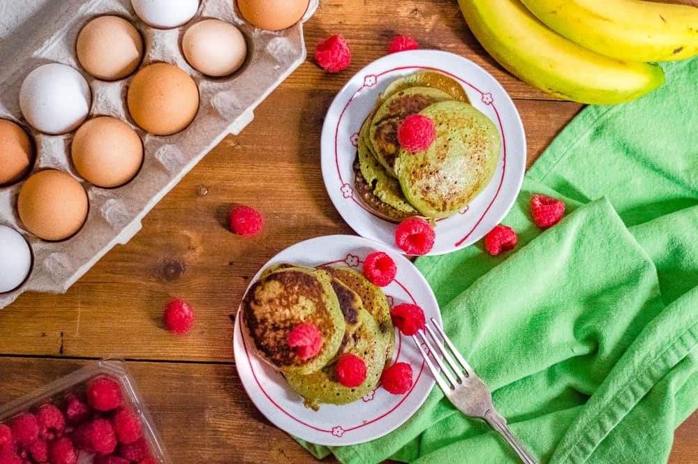 Overhead on the delicious Flourless Green Blender Pancakes presented with bananas, raspberries and eggs around the plate.