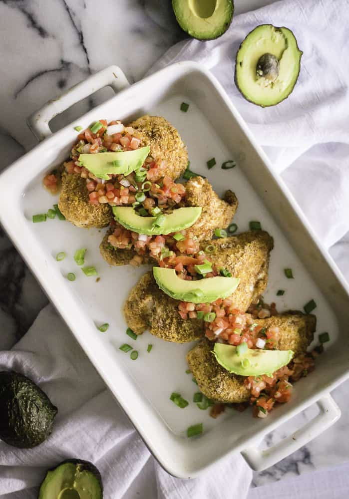 Overhead on the delicious healthy baked salsa chicken in a big white tray with avocado halves around it