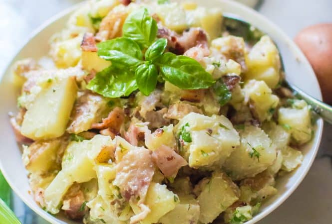 Closeup on a big white bowl full of the delicious Bacon & Herb Potato Salad