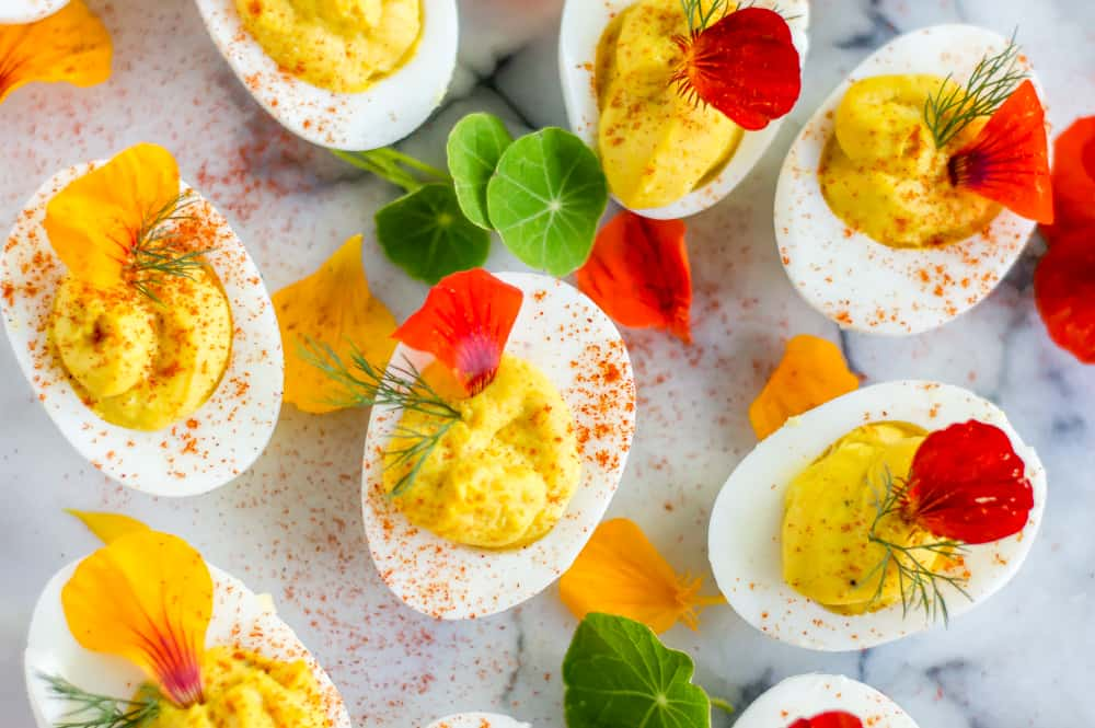 Closeup of the colorful turmeric deviled eggs decorated with beautiful petals