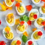 Overhead on plenty of delicious turmeric deviled eggs decorated with beautiful petals and looking extra bright and yummy
