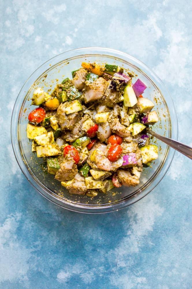 Mixing ingredients to make One-Sheet Pan Pesto Chicken & Summer Veggies