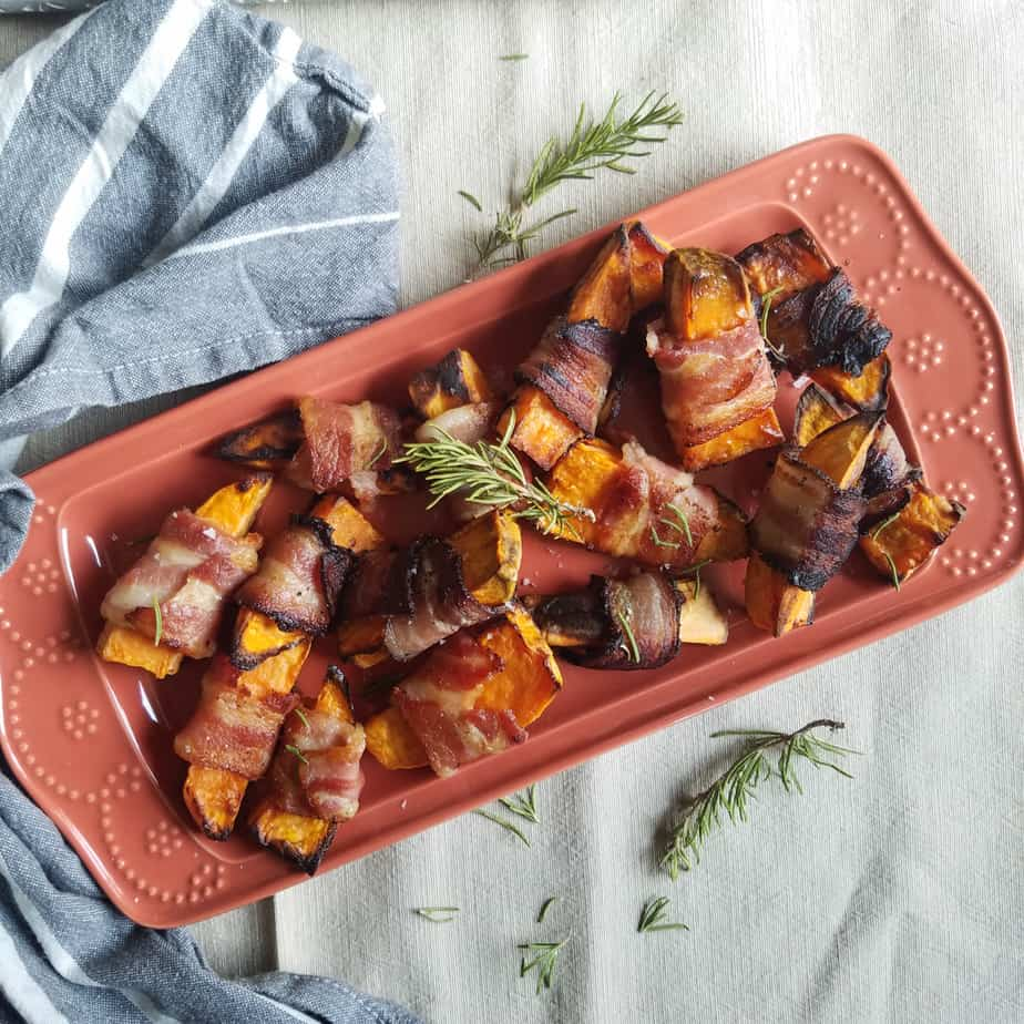 A big beautiful tray full of the delicious bacon wrapped sweet potatoes decorated with a sprig of rosemary