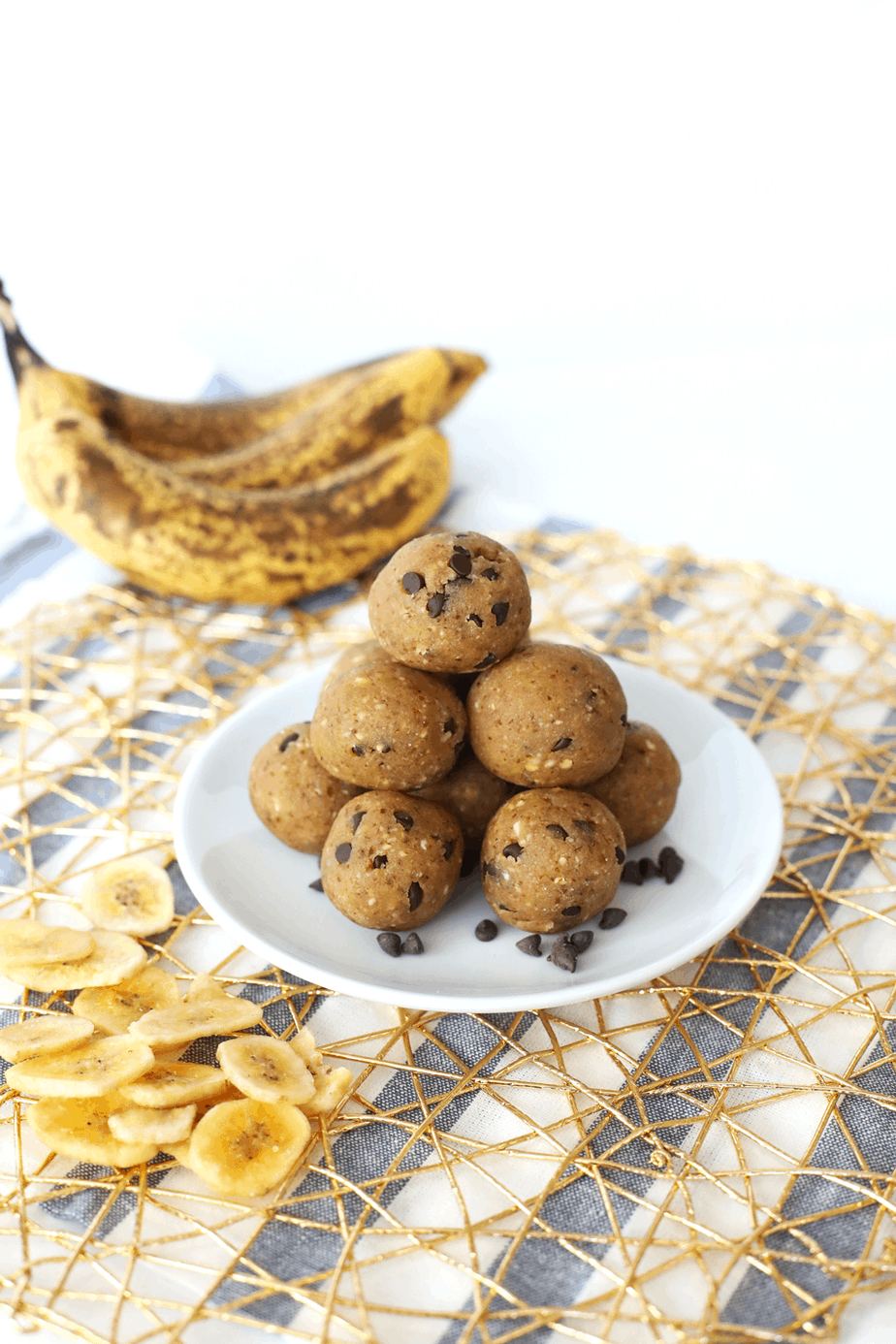 Delicious Banana Chocolate Chip Energy Balls served in a stack on a plate with banana chips on the side.