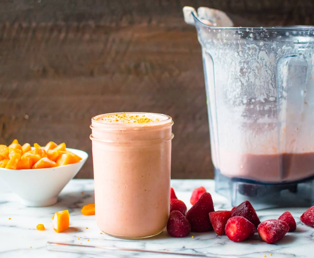 A jar full of the healthy Sunrise Butternut Squash Smoothie with a mixer that was used to make it on the same table