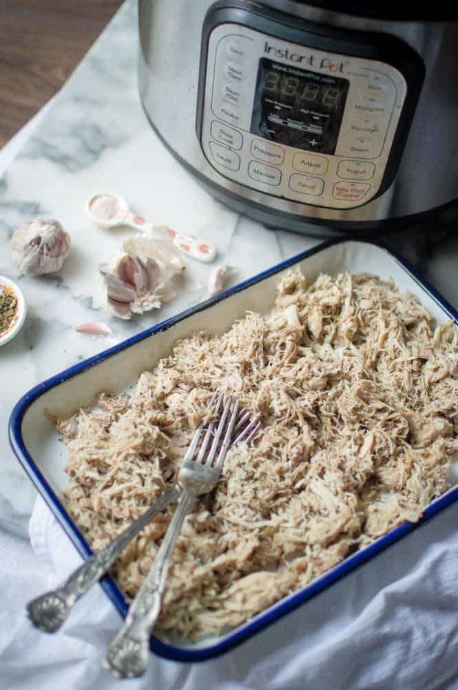 Instant Pot Garlic Herb Pulled Chicken in a light tray next to the Instant Pot and garlic cloves scattered around