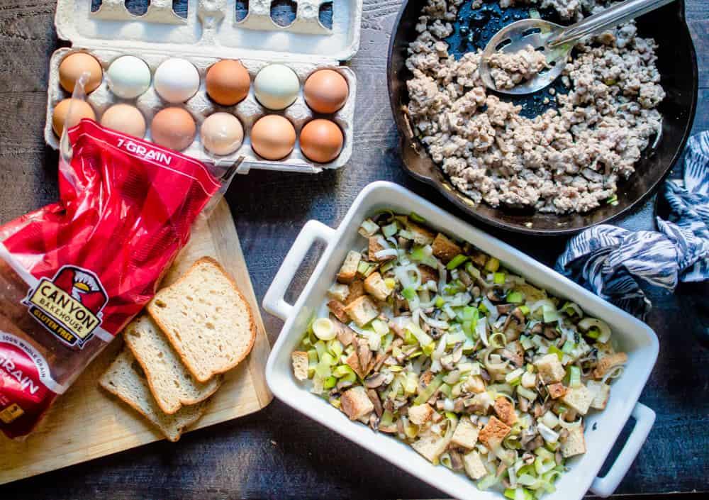 Sausage Leek & Mushroom Breakfast Casserole ingredients with twelve eggs next to a pan with sausage