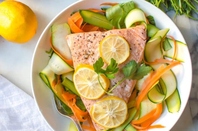 Overhead on the delicious Instant Pot Lemon Garlic Salmon served in a white plate with two lemons on the side