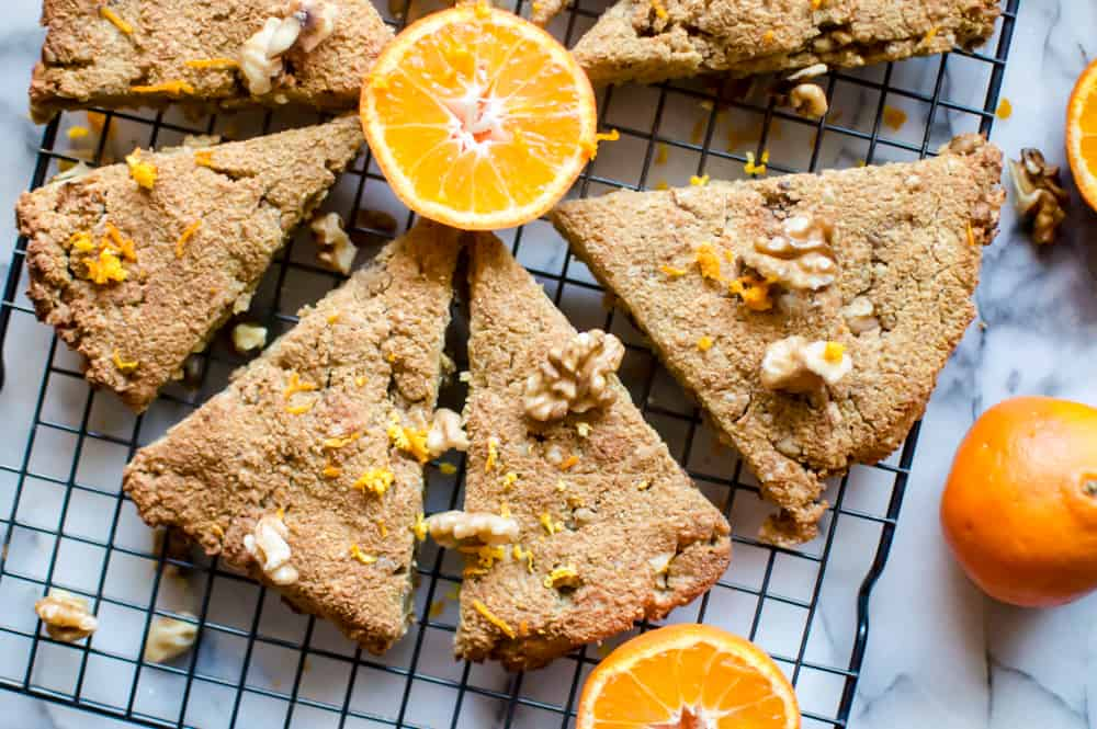 Six Paleo Orange Walnut Scones served in the morning with a few oranges on a rack