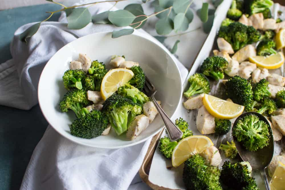 Transferring Whole30 Lemon Chicken & Broccoli from a sheet-pan to a white bowl and topping it with a lemon slice
