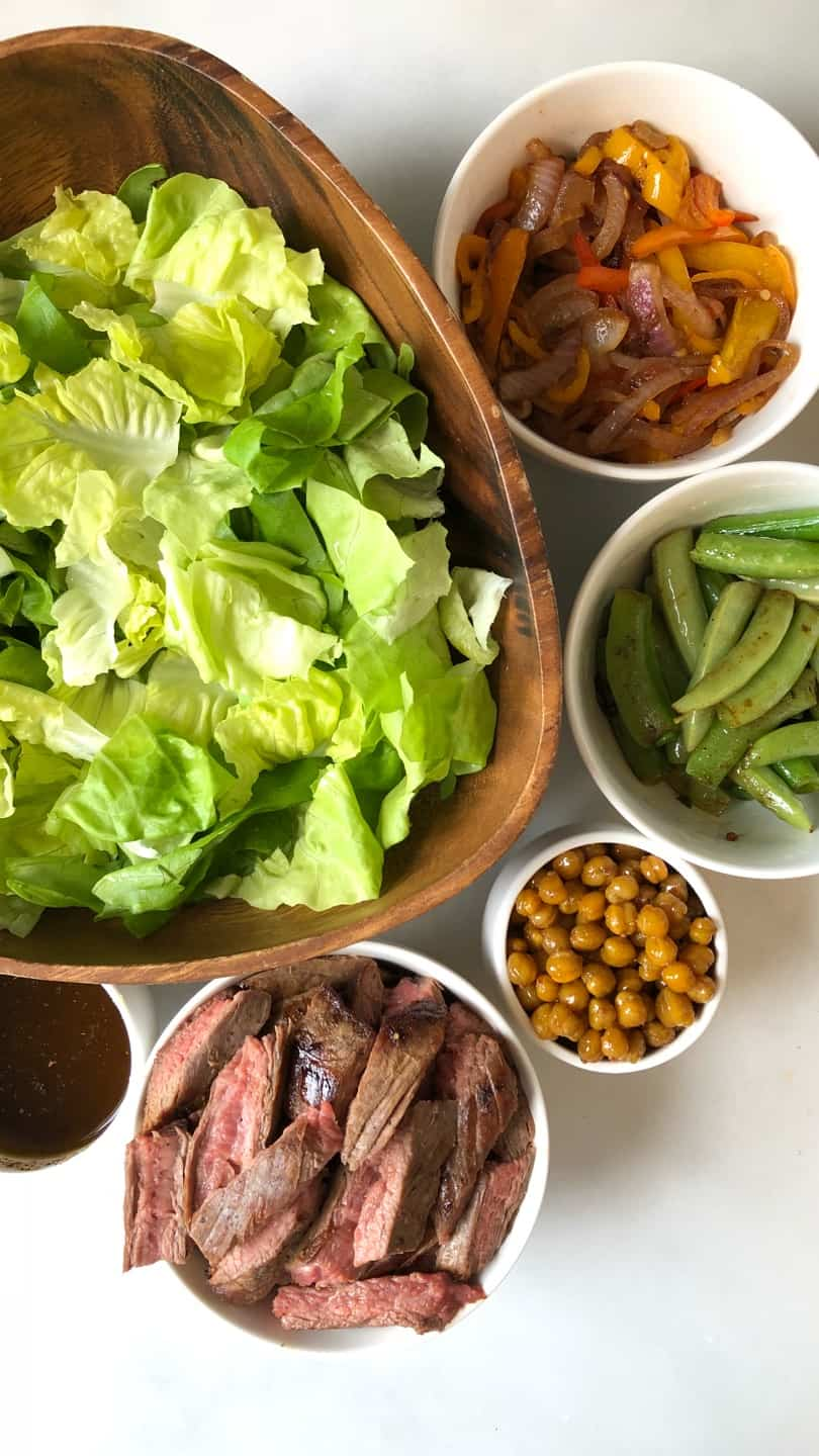 All the ingredients that you need for making this delicious fajita salad with roasted chickpeas placed in separate bowls.