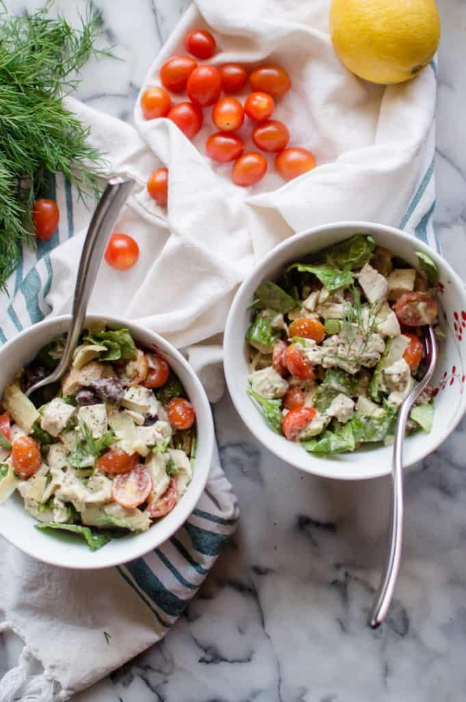 Whole30 Greek Chicken Salad served in two white bowls with more tomatoes and a lemon next to them