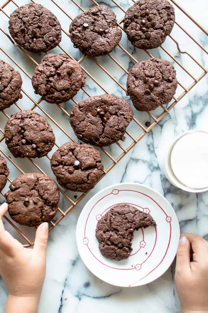 Cute little hands reaching for one of the Vegan Chocolate Almond Butter Cookies with another one in a small plate already missing one bite