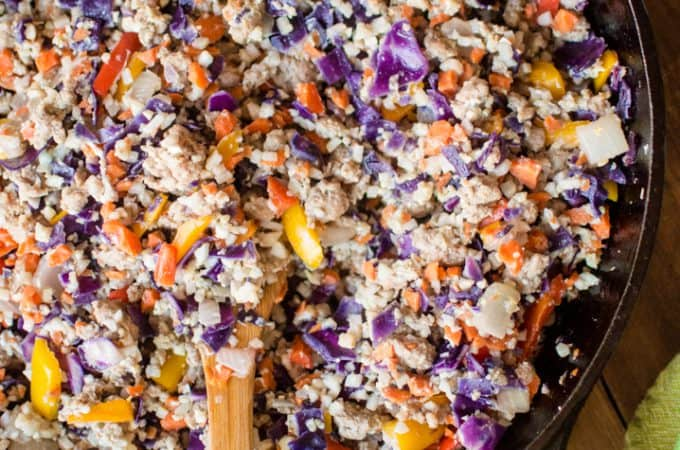 Overhead on the delicious 20-Minute Pork Fried Cauliflower Rice served in a pan with a wooden spoon inside the pan