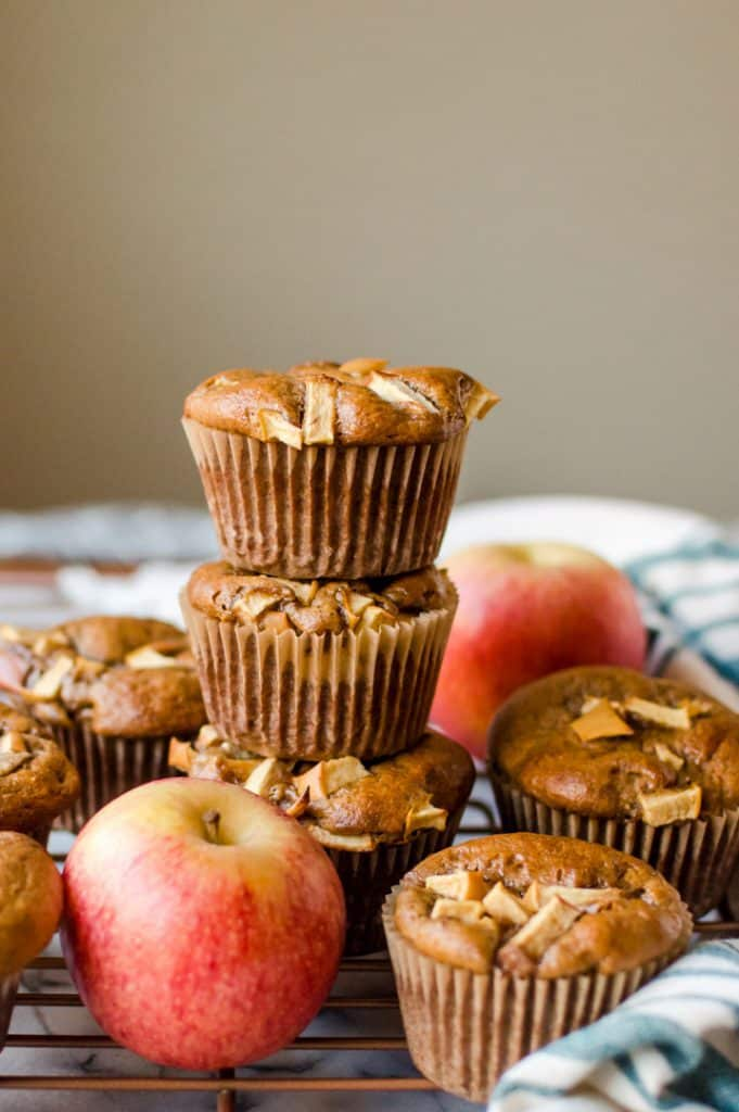 Healthy Paleo Apple Cinnamon Muffins served on top of each other with a couple of fresh apples around