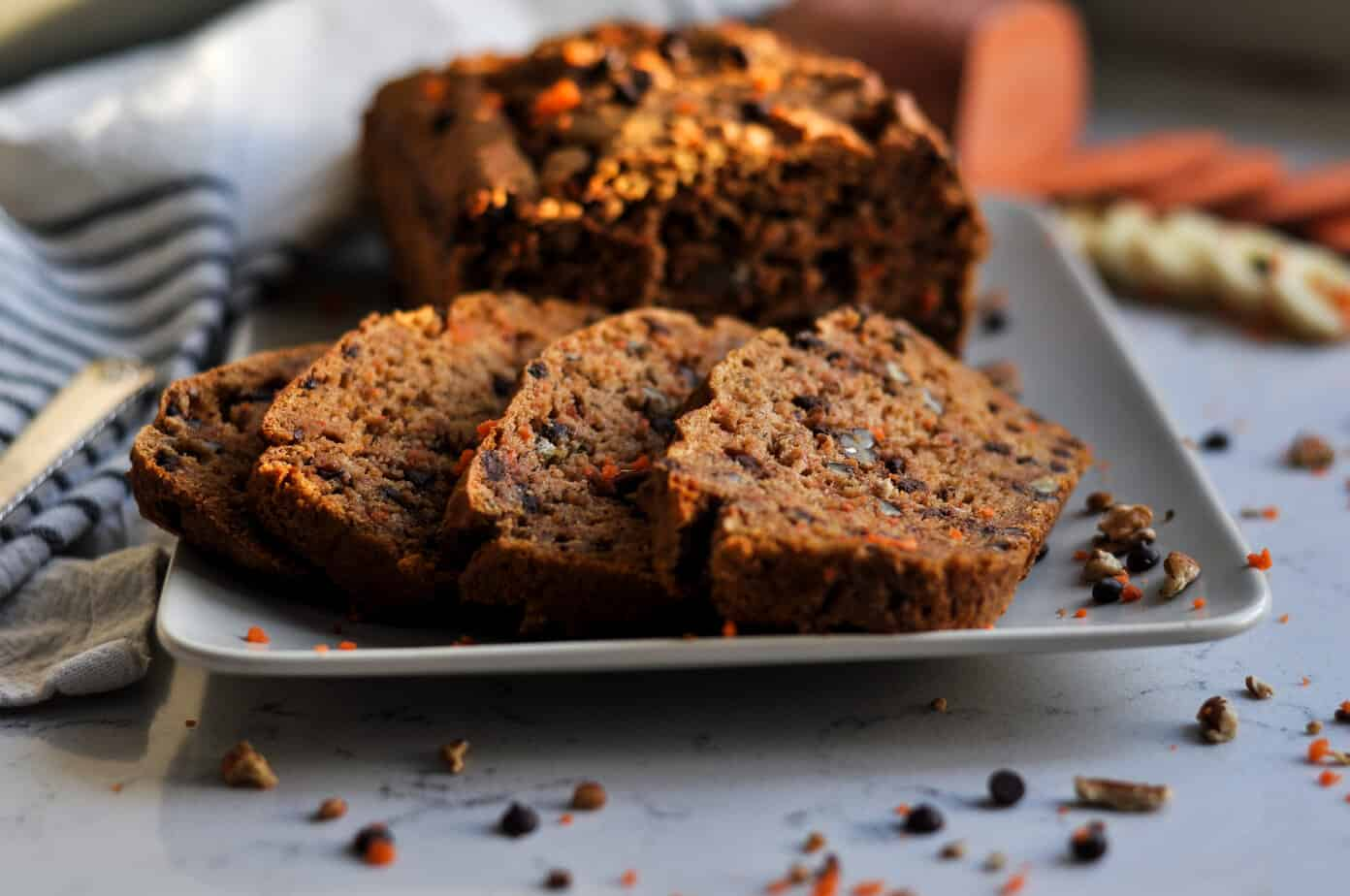 Chocolate chip carrot bread looking extra inviting and healthy with veggies blurred in the background.