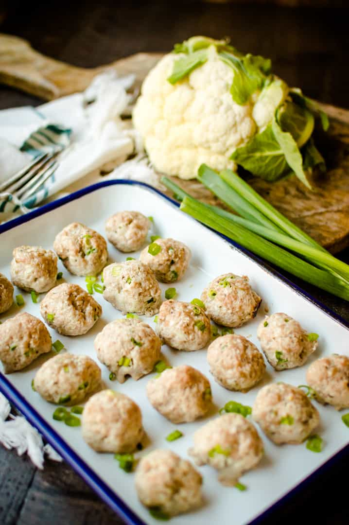 Baked hot chicken cauliflower meatballs straight out of the oven with green onions next to the tray and a head of cauliflower on a wooden table in the background